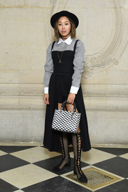 Aimee Song completed her eclectic look with a pair of black fishnet lace-up boots, also by Dior.