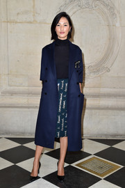 Nicole Warne looked perfectly polished in a navy coat, a black turtleneck, and a bedazzled green skirt at the Christian Dior fashion show.