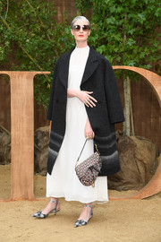 Erin O'Connor accessorized with a stylish printed purse by Dior.