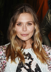 Elizabeth Olsen stuck to her usual center-parted waves when she attended the Christian Dior Cruise show.