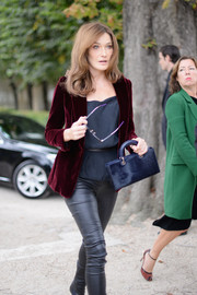 Carla Bruni-Sarkozy accessorized with a navy velvet purse by Dior for the label's Spring 2017 show.