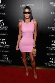 Kim Kardashian flaunted her famous curves in a pink latex mini dress by Versace at the Christie's x What Goes Around Comes Around 25th anniversary auction preview.