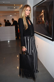 Elle MacPherson carried a black fringed tote to Chrome Hearts celebrates The Miami Project during Art Basel.