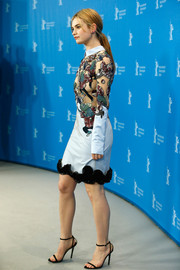 Lily James teamed her head-turning dress with simple black skinny-strap sandals by Jimmy Choo.