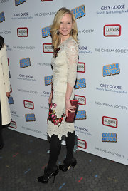 Anne Heche accentuated the red embroidery in her lacy frock with a red sparkly clutch.