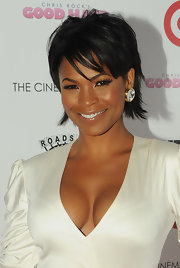 Nia Long paired her white wrap dress with large diamond studs.
