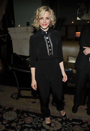 Rachel is inspired by school boy style in a black jumpsuit with a bow tie for the 'Midnight in Paris' party.