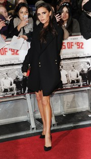 Victoria Beckham attended the 'Class of '92' premiere wearing a black wool coat from her own label.