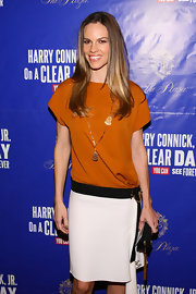 Hilary Swank opted to accessorize her drop-waist color-block dress with a black tasseled clutch.
