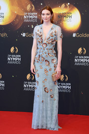 Eleanor Tomlinson polished off her look with a gold box clutch.