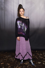 Sasha Lane layered a patterned boatneck sweater over a printed maxi dress, both by Coach, for the brand's Fall 2018 show.