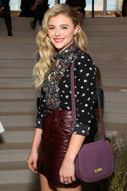 Chloe Grace Moretz arrived for the Coach fashion show carrying a purple satchel from the brand.