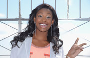 Coco Jones chose a pair of shoulder-grazing white dangling earrings to go with her color-blocked outfit when she visited the Empire State Building.