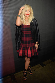 Rita Ora looked flirty-edgy at the DKNY fashion show in a red and black tartan dress with a box-pleated hem, which she wore with a leather jacket.