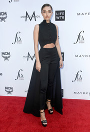 Delilah Belle Hamlin hit the 2018 Fashion Los Angeles Awards wearing a black top that was cropped high at the front before dipping down to the ankles at the back.
