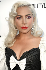 Lady Gaga teamed her bright eyeshadow with a bold red lip.