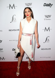 Olivia Culpo chose an ultra-modern white Baja East wrap dress, featuring an asymmetrical hem and a printed sash, for her Fashion Los Angeles Awards look.