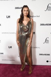 Irina Shayk kept the shine going with a pair of gold triple-strap heels.