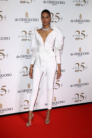 Cindy Bruna opted for a white Yolancris jumpsuit with puffed sleeves and a bowed waist when she attended the De Grisogono party during Cannes.