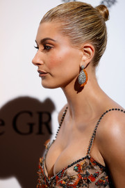 Hailey Baldwin attended the De Grisogono Love on the Rocks party wearing her hair in a classic bun.