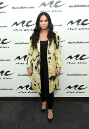 Demi Lovato visited Music Choice looking chic in a yellow and black jacquard coat.