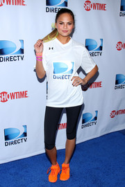 Chrissy Teigen attended the DirecTV Beach Bowl wearing a pair of sneakers in an eye-catching orange hue.