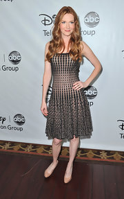 Darby accessorized her bold graphic dress with subtle nude pumps.