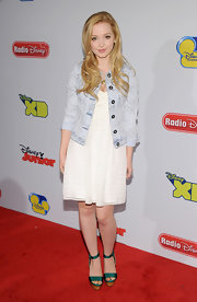 Dove Cameron chose this light wash denim jacket to pair with her white sun dress for a youthful and feminine red carpet look.