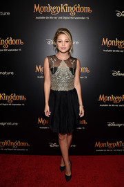 Olivia Holt went for ladylike elegance in a lace-accented black and gold cocktail dress by Marchesa Notte at the 'Monkey Kingdom' special screening.