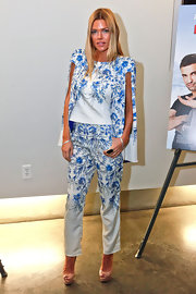 Sophie Monk showed that she's not afraid of color and prints when she sported this floral print cape and matching pant.