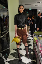Liu Wen added a pop of color with a yellow leather purse by Prada.