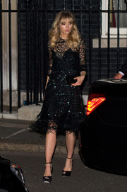 Suki Waterhouse paired her sophisticated dress with black platform peep-toe heels.