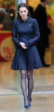 Kate Middleton wore a pleated navy Orla Kiely skirt with her tailored jacket, completing her look with a feminine touch.