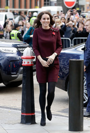 Kate Middleton kept it prim and proper at the Place2Be School Leaders Forum in a loose maroon dress with gold buttons along one shoulder.