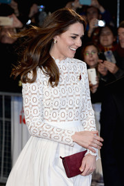 Kate Middleton accessorized with a burgundy suede clutch by Mulberry for a pop of color to her white outfit at the UK premiere of 'A Street Cat Named Bob.'
