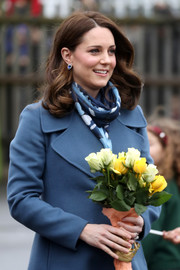 Kate Middleton paired a printed scarf by Beulah London with a blue wool coat for her visit to Roe Green Junior School.