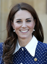Kate Middleton accessorized her dress with an elegant gold brooch.