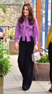 Kate Middleton looked demure in a long-sleeve purple pussybow blouse by Gucci while visiting the Henry Fawcett Children's Centre.