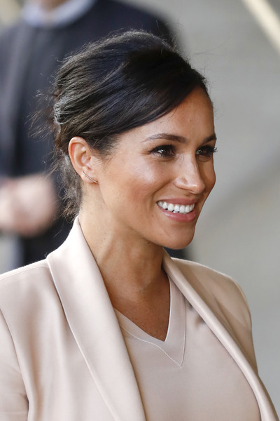 Meghan Markle stuck to her signature messy updo when she visited the National Theatre.