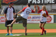 Carrie Underwood (R) gets a high-five from teammate Shane Tallant (center) as David Nail looks on from second base during City of Hope?s 22nd annual Celebrity Softball Challenge during CMA Fest on June 9, 2012 in Nashville .