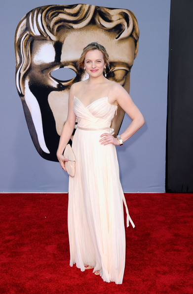 Elisabeth Moss teamed her elegant nude gown with a matching Lotte envelope clutch in blush crepe de chine.