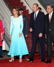Kate Middleton touched down in Pakistan wearing a blue ombre dress with a draped neckline and matching trousers underneath.