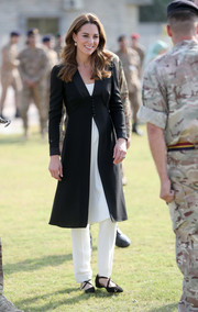 Kate Middleton visited the Army Canine Centre in Islamabad, Pakistan wearing a black Beulah London coat over a white tunic and trousers.