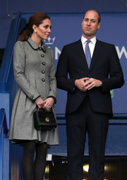 Kate Middleton paired a black Aspinal of London croc purse with a gray coat dress for her visit to Leicester City Football Club.