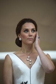 Kate Middleton paired her lovely 'do with huge faux-pearl studs by Balenciaga.