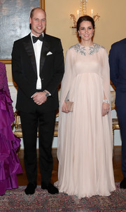 Kate Middleton paired her elegant dress with a nude suede clutch by Jimmy Choo.