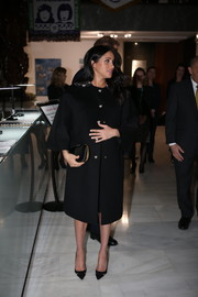 Meghan Markle finished off her all-black ensemble with a satin clutch by Gucci.