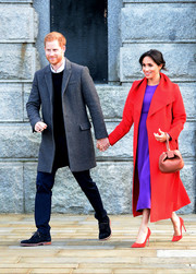 Meghan Markle matched her coat with a pair of red Stuart Weitzman pumps.