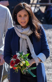 Meghan Markle styled her outfit with a gray scarf by Wilfred for a tour of Asni, Morocco.