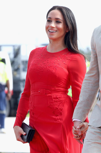 Meghan Markle paired a black Dior leather clutch with a long-sleeve red dress for her arrival in Tonga.